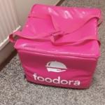 En rosa kylväska med Foodora-tryck.