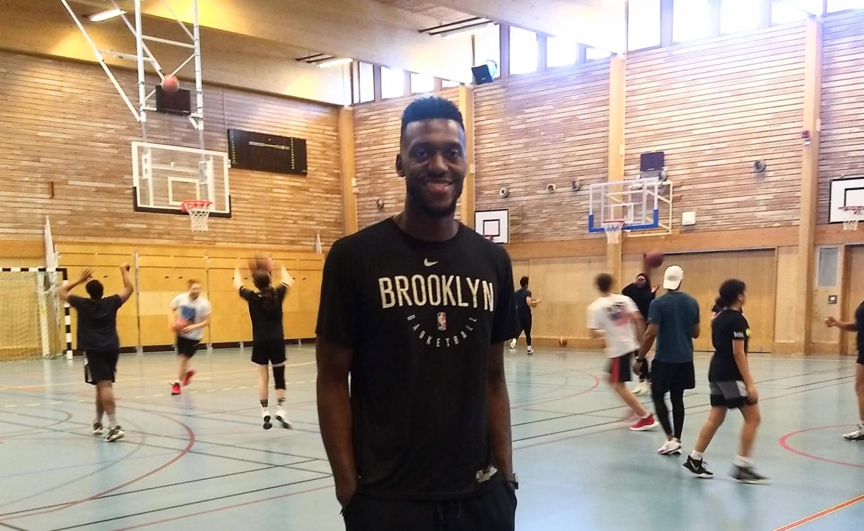Mike Moore med basketspelande ungdomar i bakgrunden