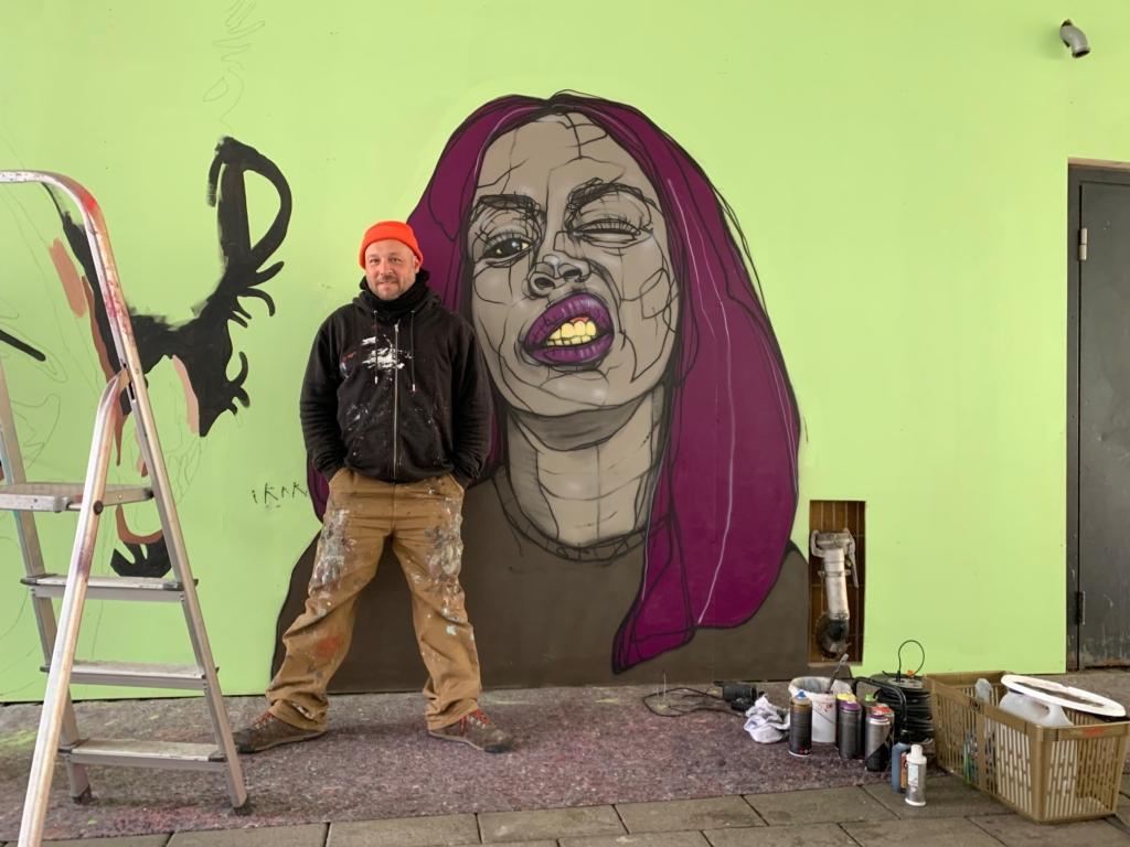 konstnären framför målningen av Imenella.
