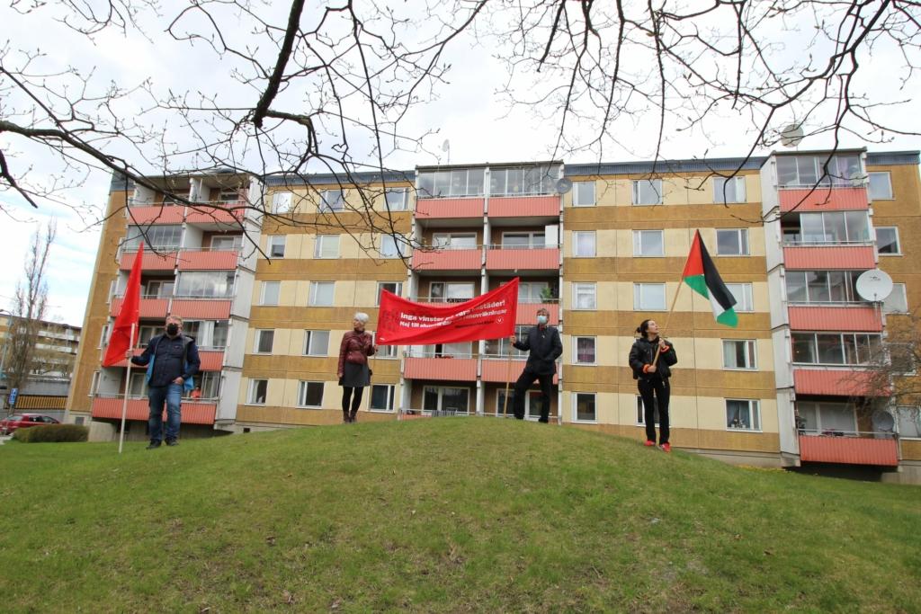 vänsterpartister med en röd banderoll och palestinaflagga