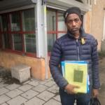 Eritreansk man med en massa dokument i handen.