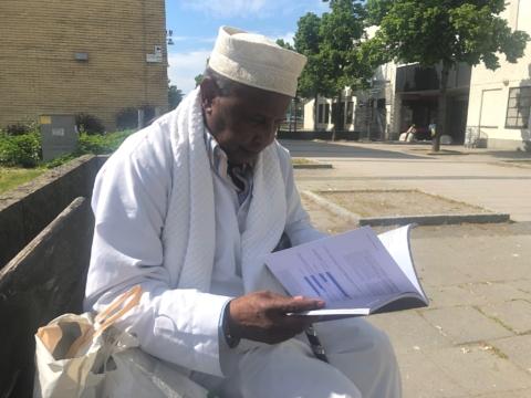 Man i muslimsk klädsel läser en rapport.