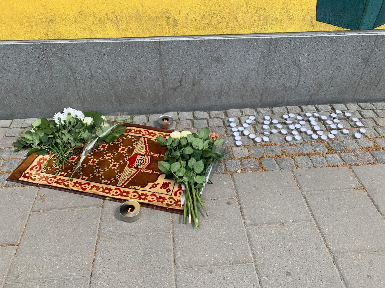 minnesplats efter den mördade i Husby. Blommor, en matta och värmeljus.