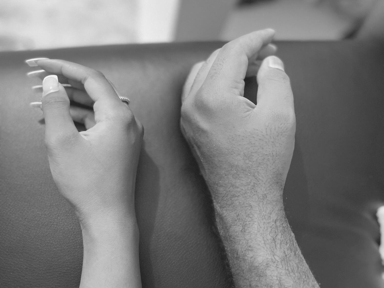 Två olika händer vilar på en soffa bredvid varandra