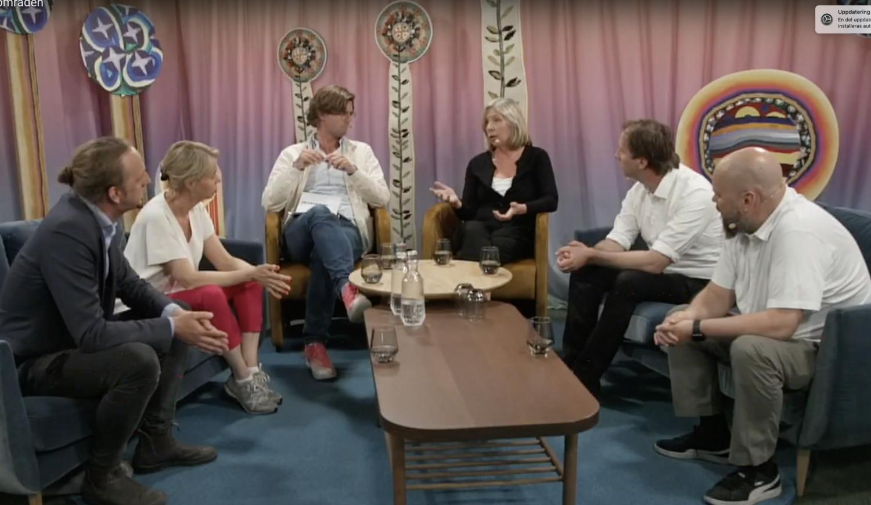 Sex personer sitter i en soffgrupp.