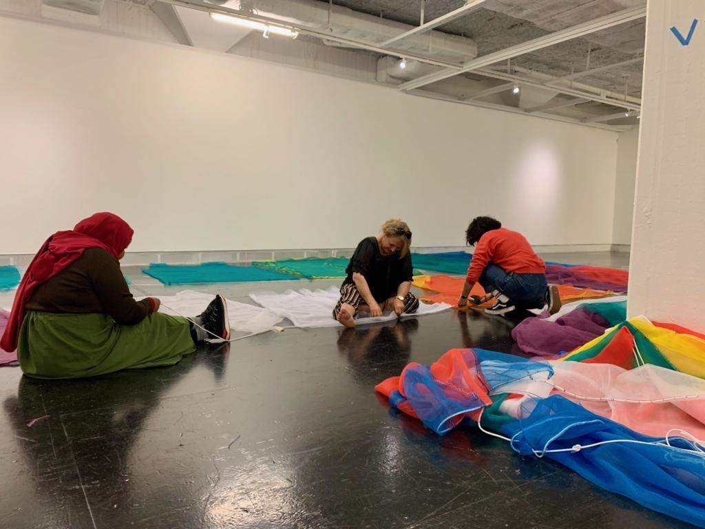 Kvinnor sitter på golvet i konsthallen och syr.