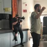 TV-fotograf filmar och man pratar i förgrunden.