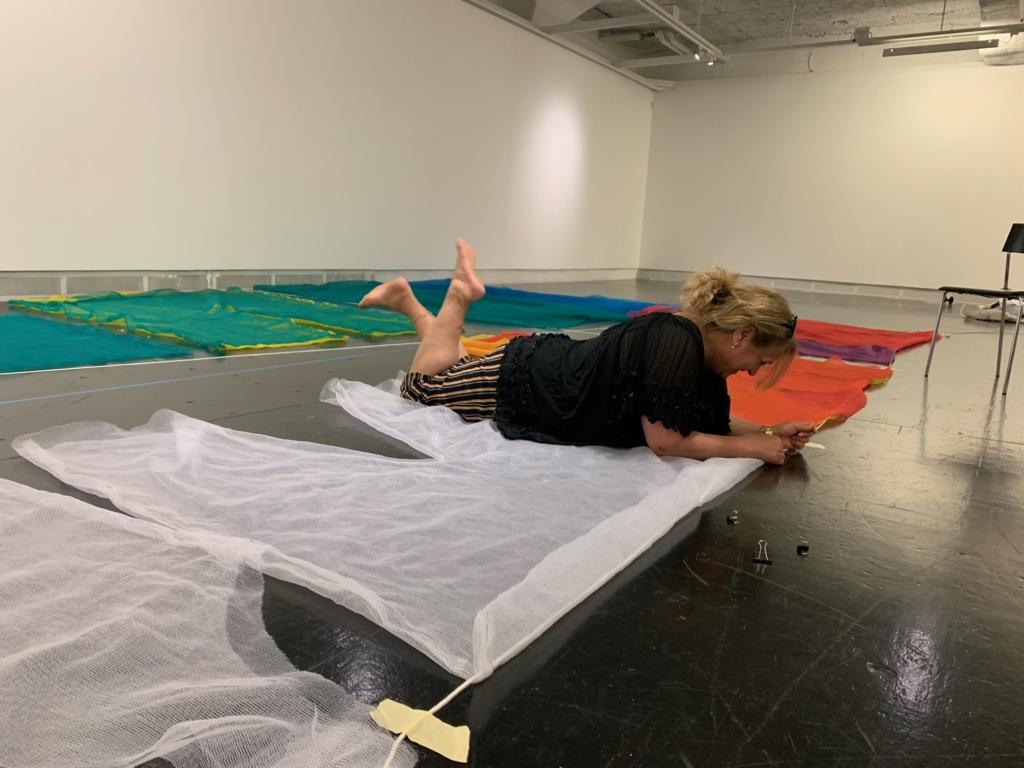 Kvinna ligger på mage på golvet bland stora tyg.