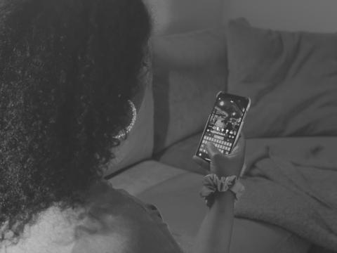 Tjej håller i telefon och tittar på Snapchat