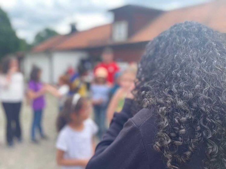 Bild där man ser en tjej bakifrån och barnen framifrån suddigt.