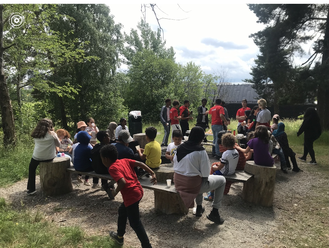 Barn och unga sitter tillsammans vid Eggeby gård.