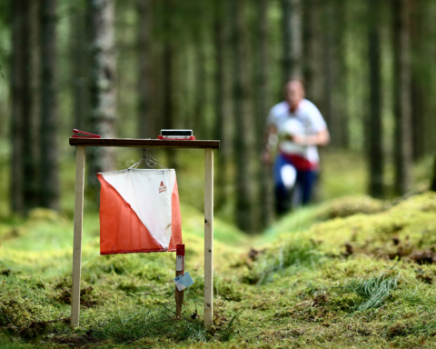 man springer i skogen och en orienteringsskärm i förgrunden.
