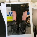en polis håller fram sina händer med handskar