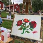 tavla med blommotiv på staffli framför husby gård
