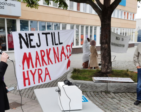 Kvinna med mikrofon och banderoll mot marknadshyra