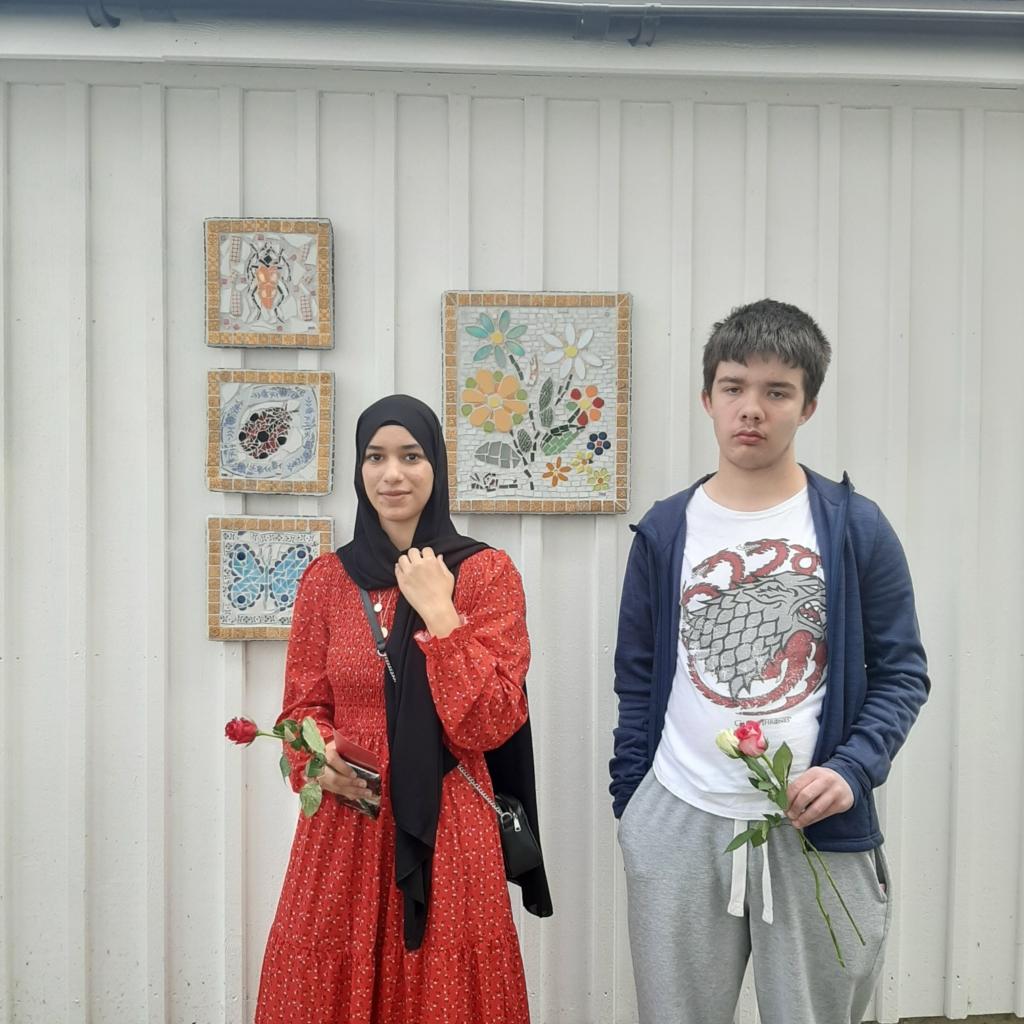 två ungdomar framför mosaik