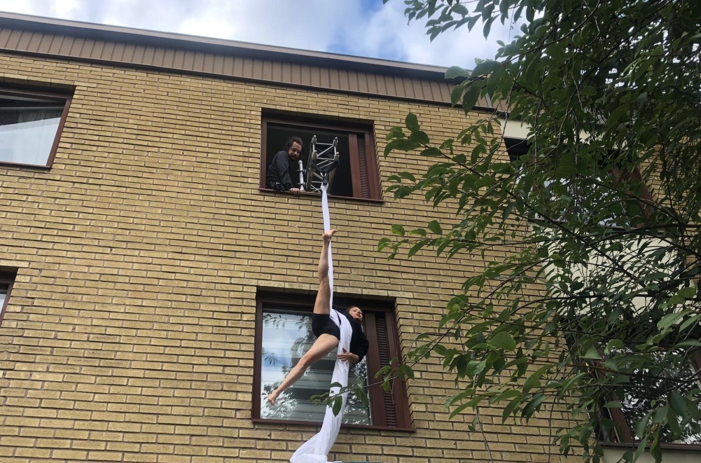 en cirkusartist hänger ut genom ett fönster i ett lakan