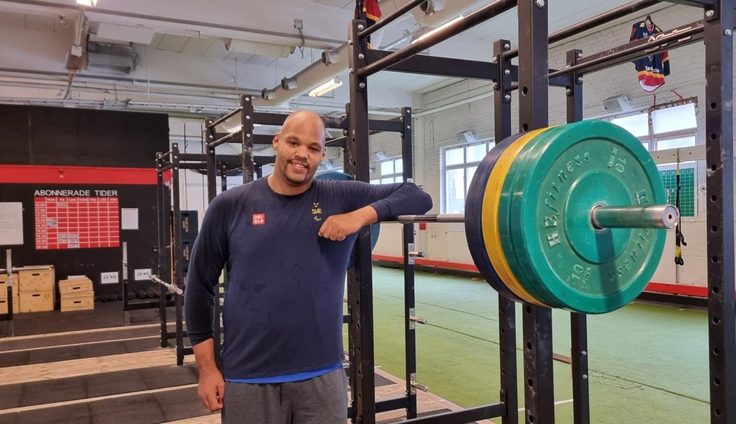 en leende man i ettt gym lutar sig mot en skivstång