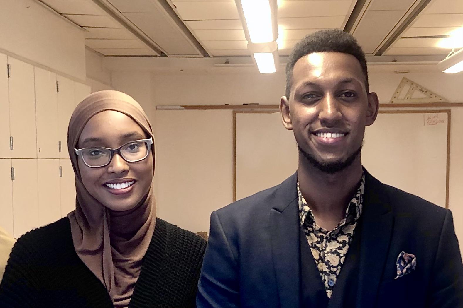 Ung kvinna i hijab och glasögon bredvid ung man i kostym. Båda ler