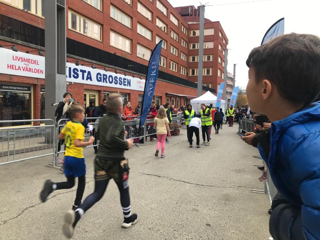 Barn som springer och mycket publik.