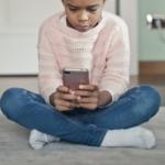 ett barn som kollar i mobilen