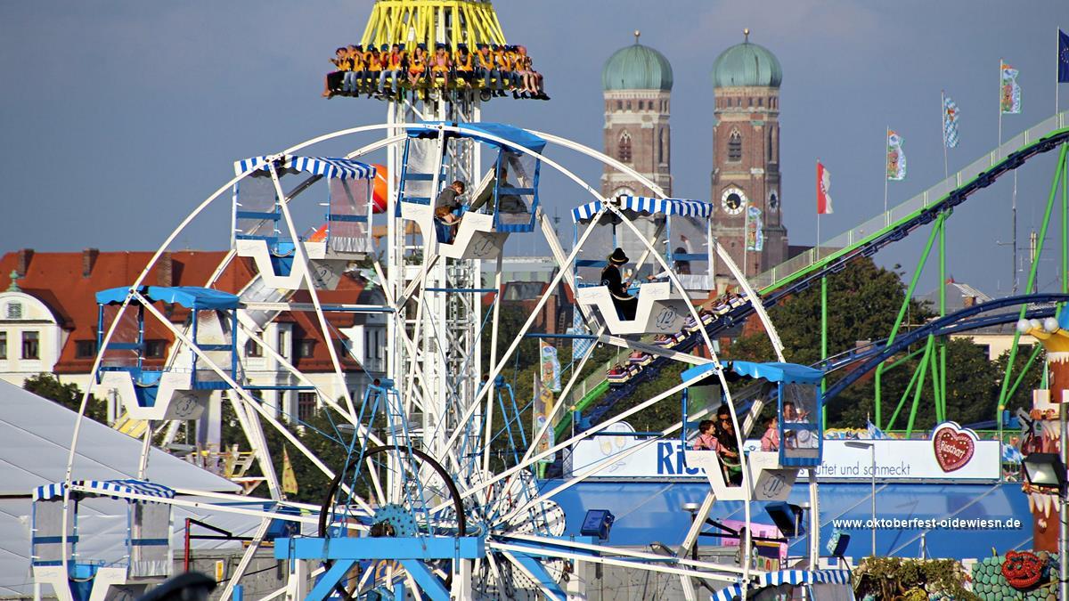 Oide Wiesn im Vordergrund - Oktoberfest Fahrgeschäfte im Hintergrund