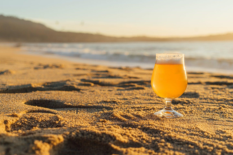 Et glass med øl som står på stranden i solsteiken.