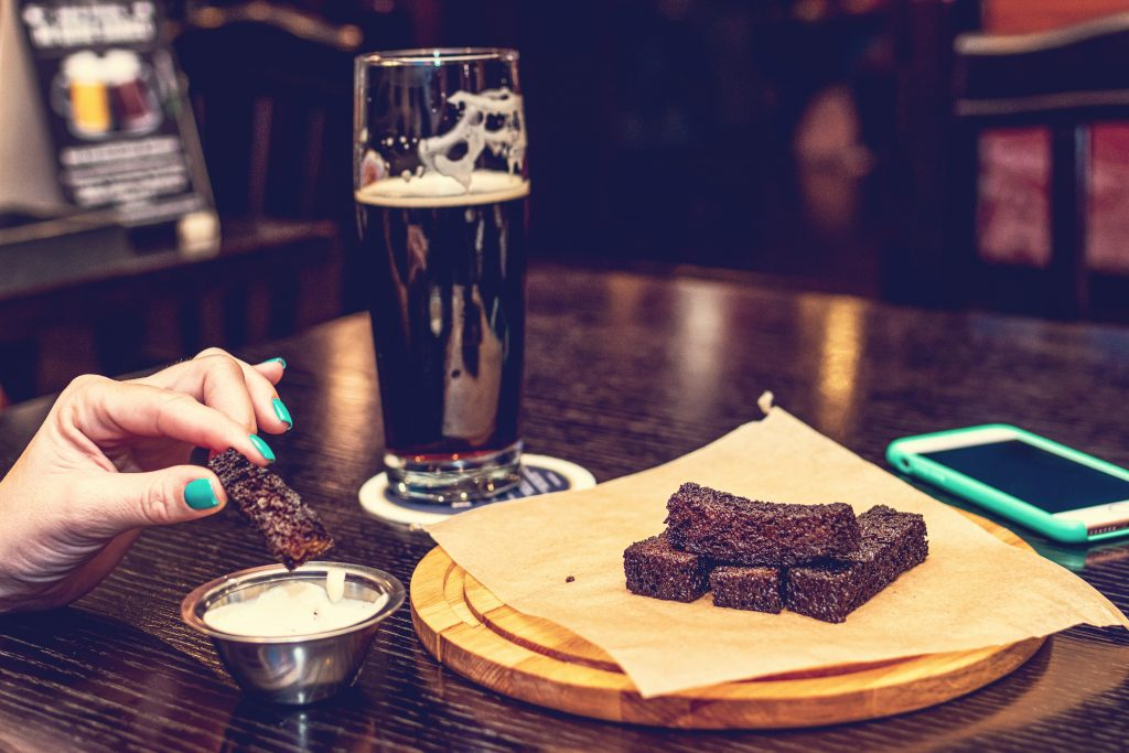 Brownie på et fat og Stout i et ølglass på bordet.