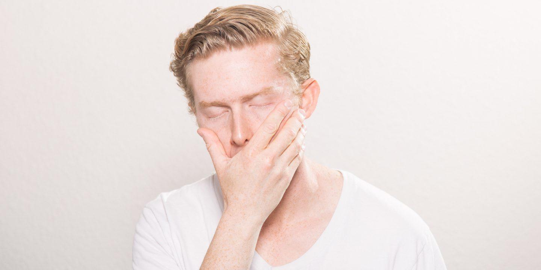 En trøtt person med hvit genser som gjesper og har øynene igjen.