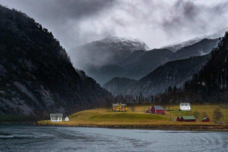 Bilde av en gård med tilhørende bygg nær vannet på Vestlandet. Fjell i bakgrunnen.