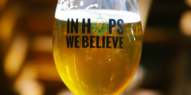 """Et glass på bordet fylt med øl. Glasset har teksten """"In Hops We Believe"""""""