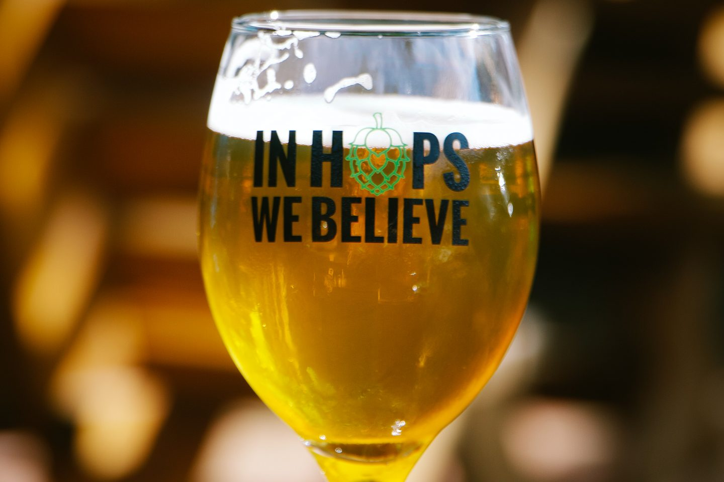 "Et glass på bordet fylt med øl. Glasset har teksten ""In Hops We Believe"""