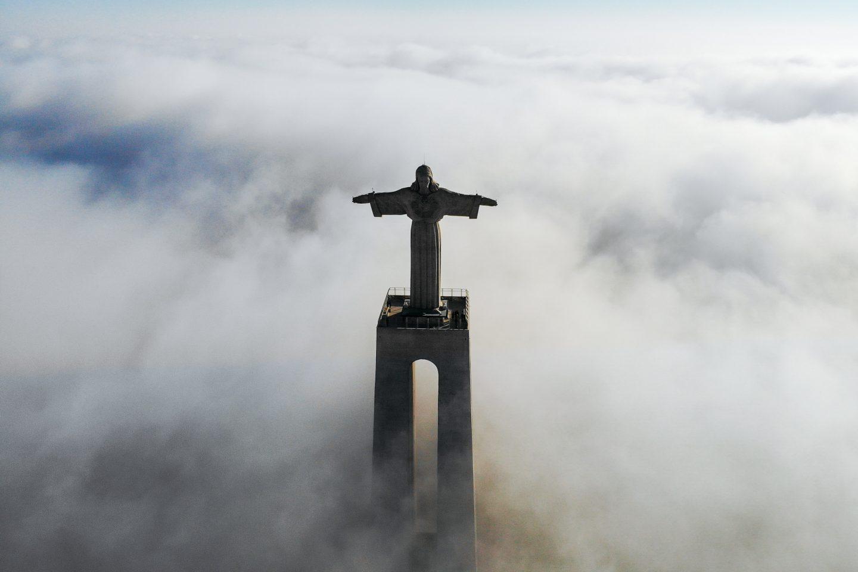 En statue av Jesus med armene ut står høyt over skyene.