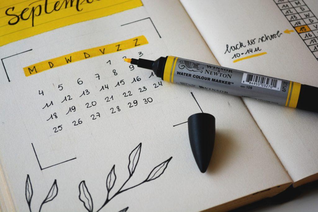 En kalenderbok med siden september oppe. En gul markørtusj ligger uten kork på boka.