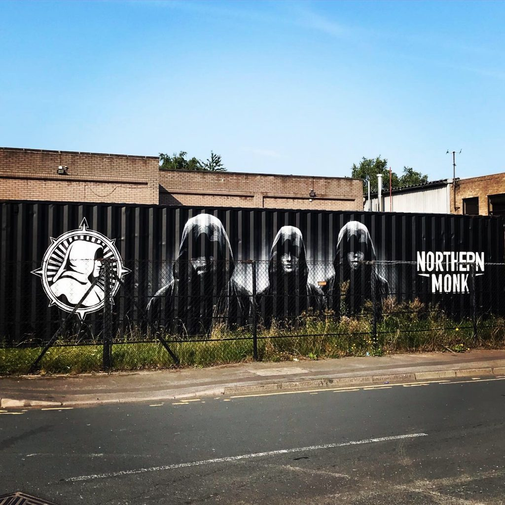 En svart container i Leeds med logoen til Northern Monk og bilde av tre skumle munker. Blå himmel. Foran bryggeriet.