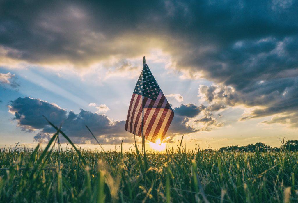 Et amerikansk flagg i solnedgangen, på en gresslette.