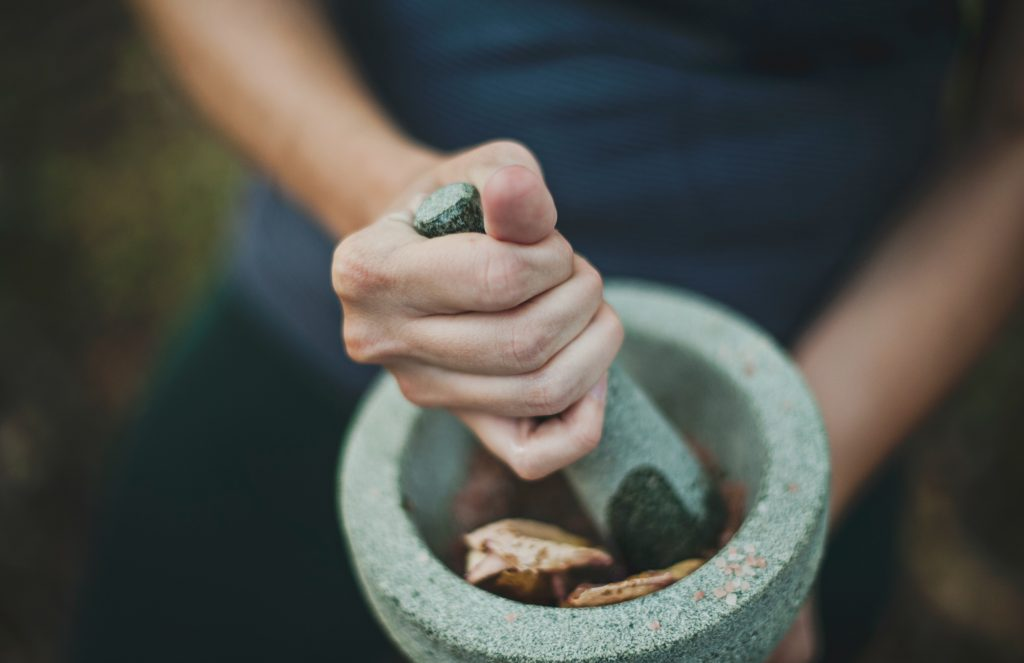 En hånd som knuser urter i et beger med en urteknuser.