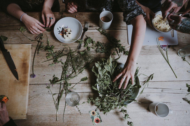 Et bord sett ovenfra. En haug med urter og to personer som blander de sammen. Kaffekopp og asjett på bordet.
