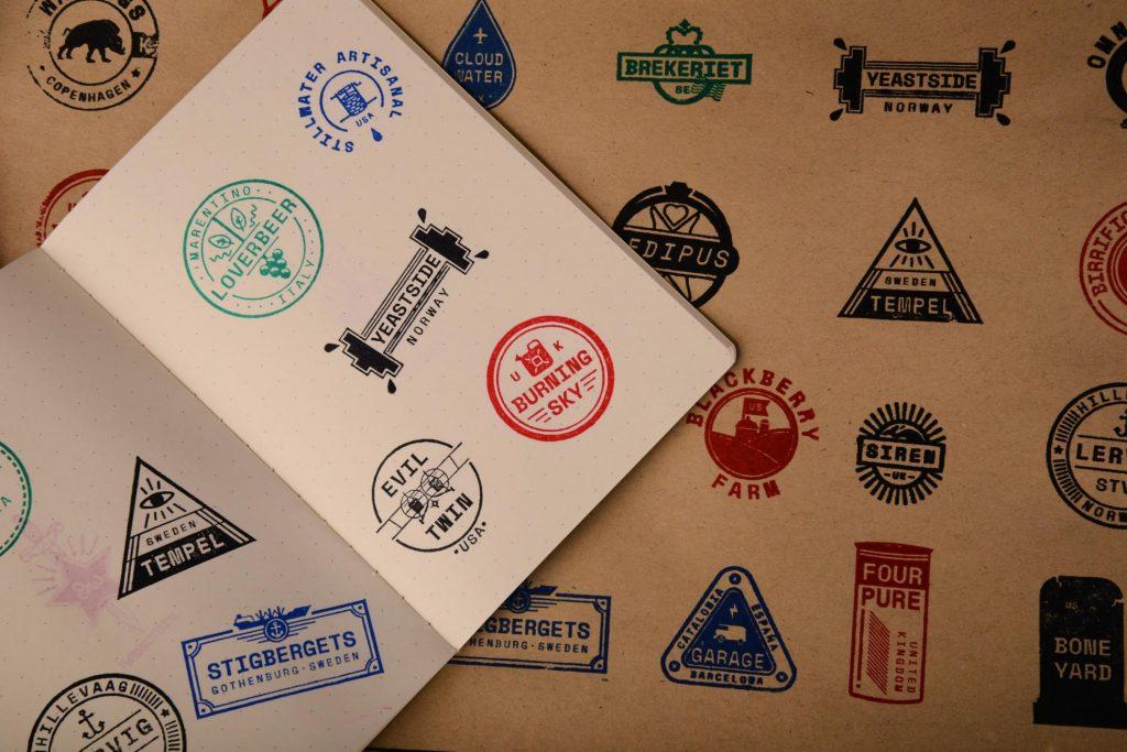 En åpen bok med mange stempel fra ulike bryggerier.