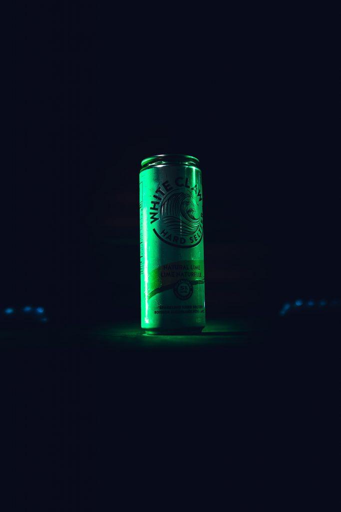 En boks med Hard Seltzeren White Claw med grønt lys med en svart bakgrunn.
