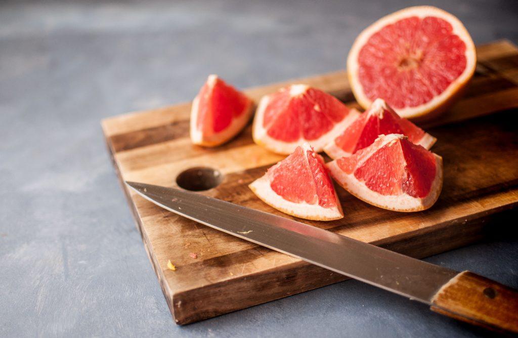 Bilde av et skjærebrett og en kniv og en oppkuttet grapefrukt på fjøla.