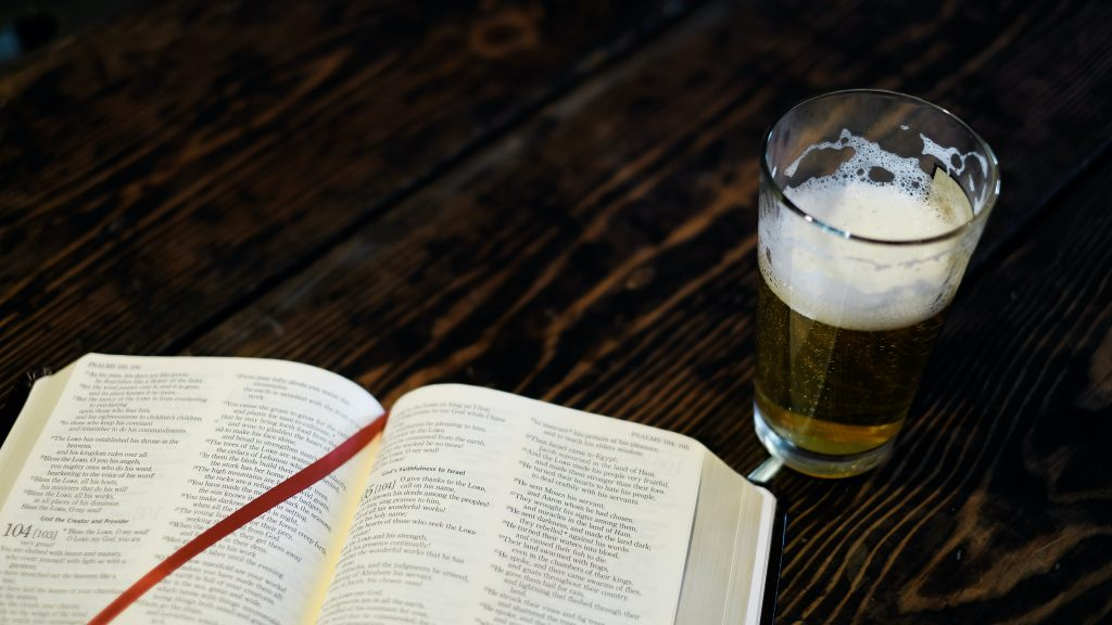 En bibel som ligger åpen, med et halvfullt ølglass ved siden av.