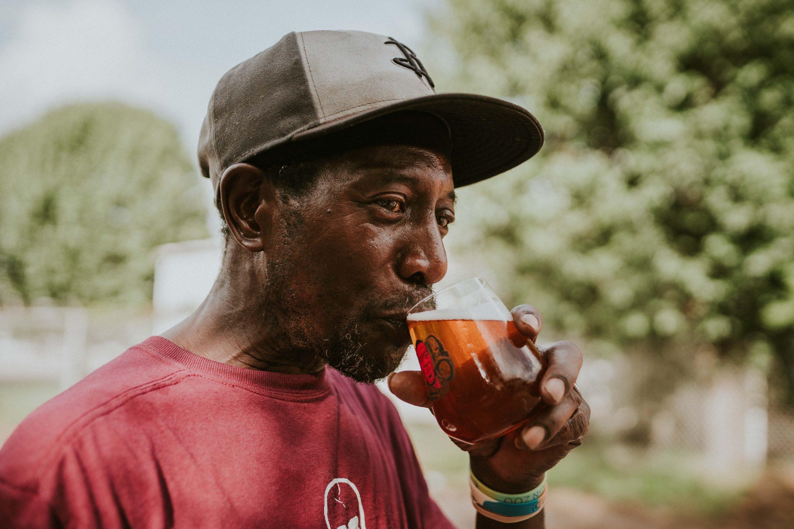 Mann med caps smaker på et glass med øl.