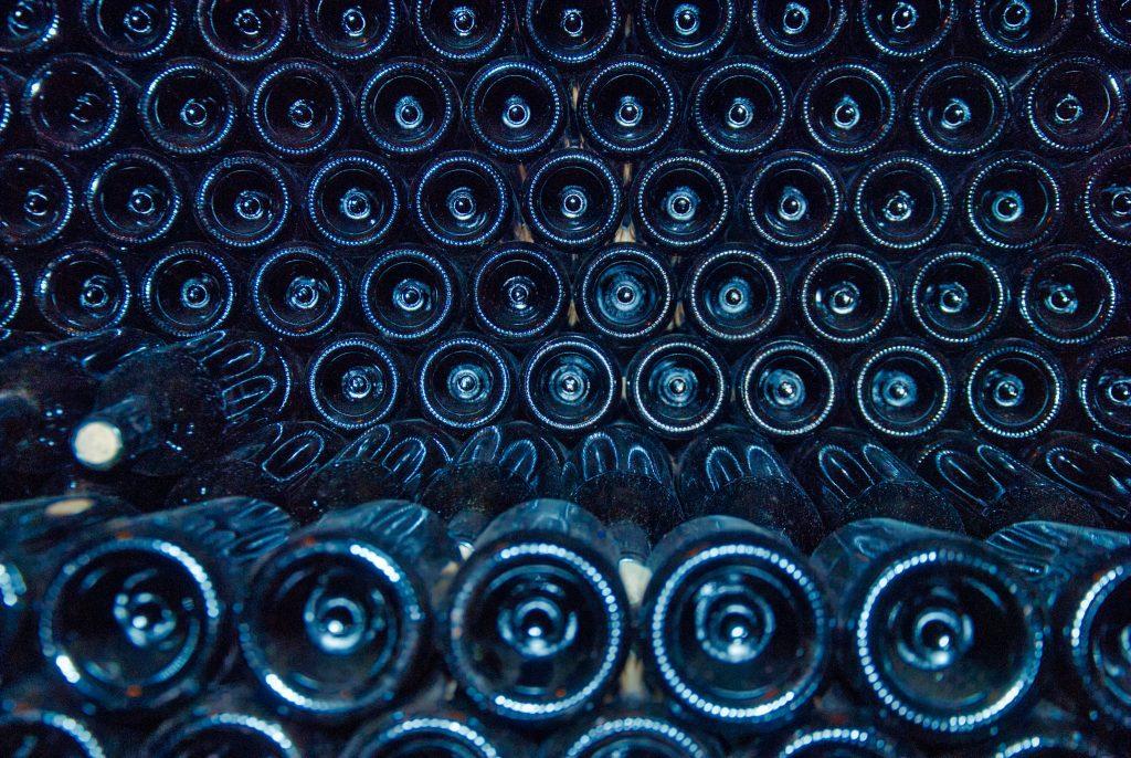 En haug med flasker som ligger i en kjeller oppå hverandre.