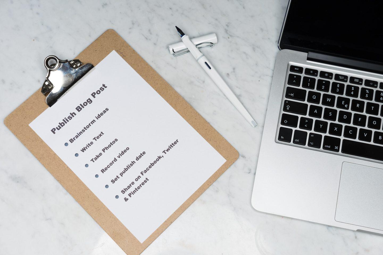 En notatblogg med sjekkliste, penn og PC.