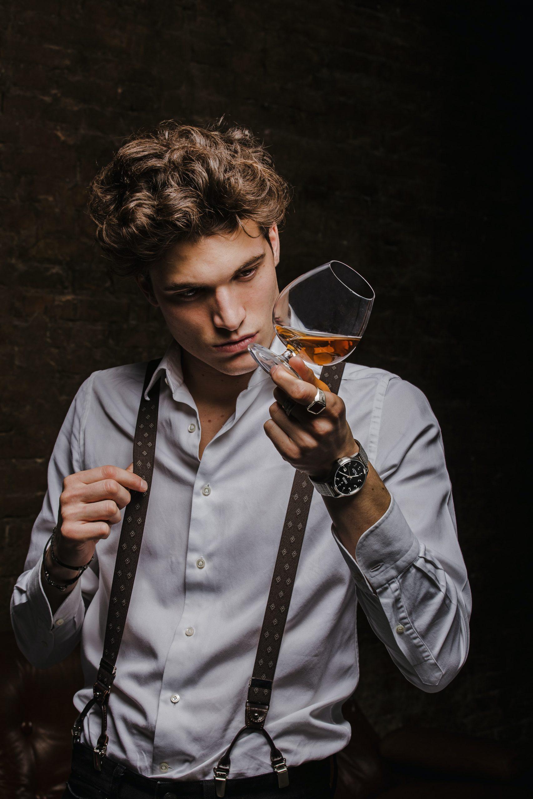En person som holder et glass med cognac skjevt og ser på glasset.