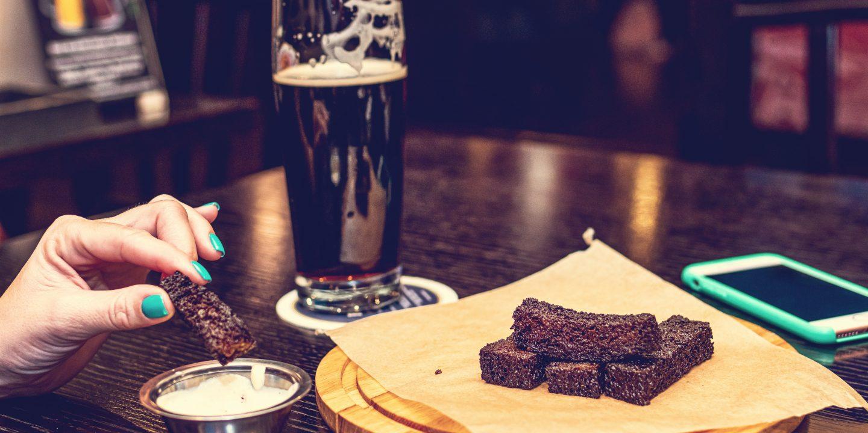 En damehånd som dypper en brownie i en type saus. Flere brownie på bordet på et fat og et glass med mørkt øl (stout) bak.