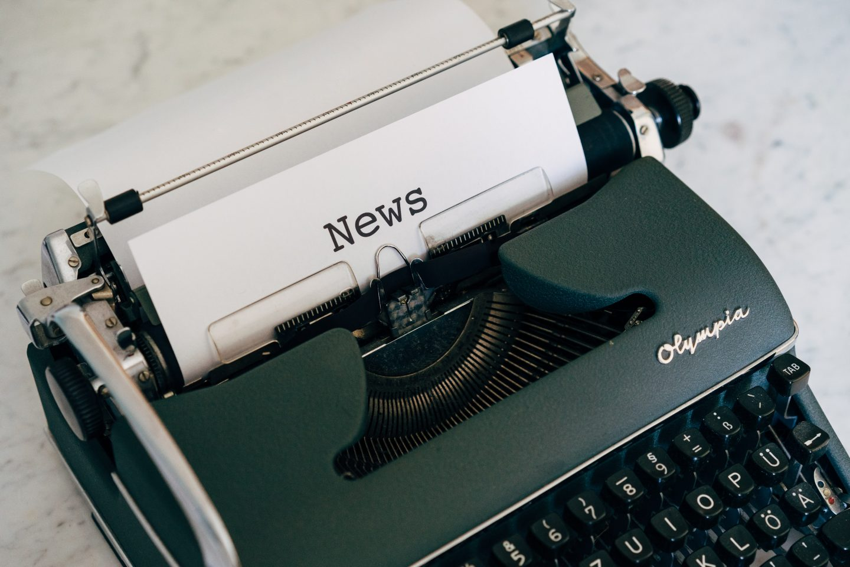 """En skrivemaskin med et ark der det er skrevet """"News""""."""