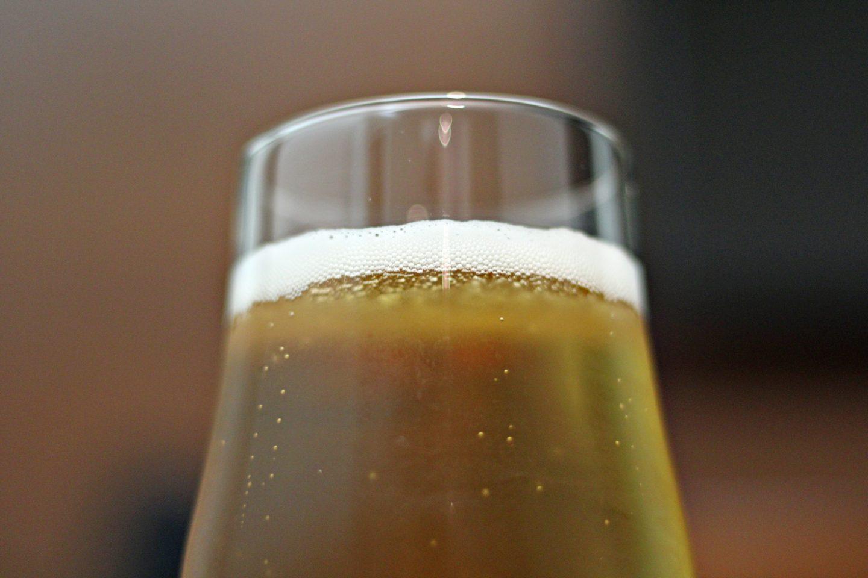 Bilde av et sprudlende glass med øl. Ser bare øverste halvdel av glasset.