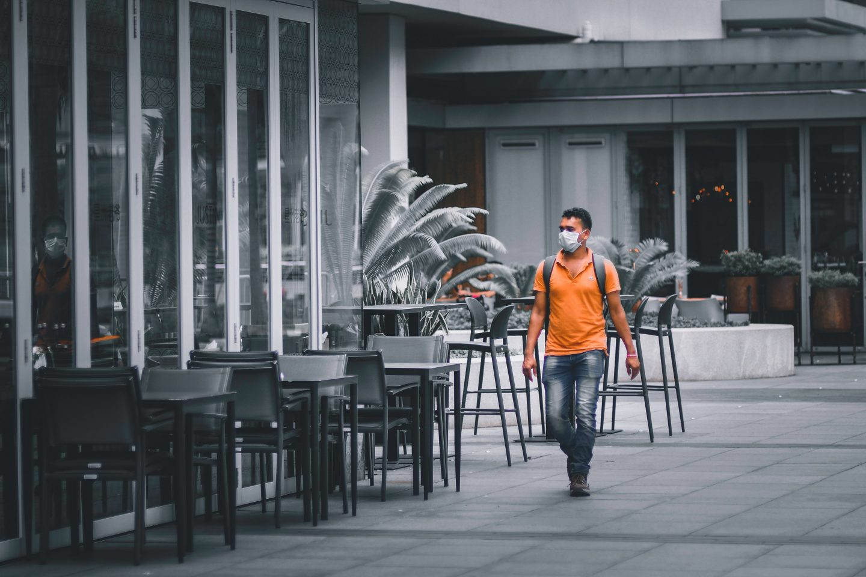 En mann med munnbind går forbi en tom restaurant.